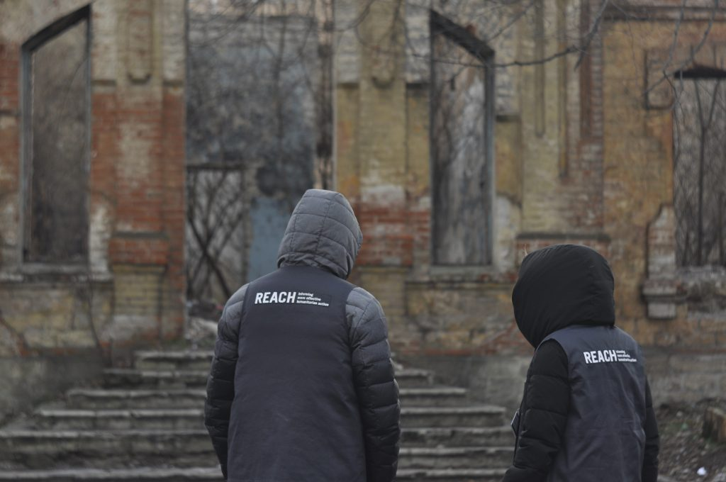 REACH Assessment Officers stand in front of the remains of a shelled building in the community of Verkhnotoretske within 5 km of the line of contact between Ukrainian armed forces and separatist groups ©REACH/2018