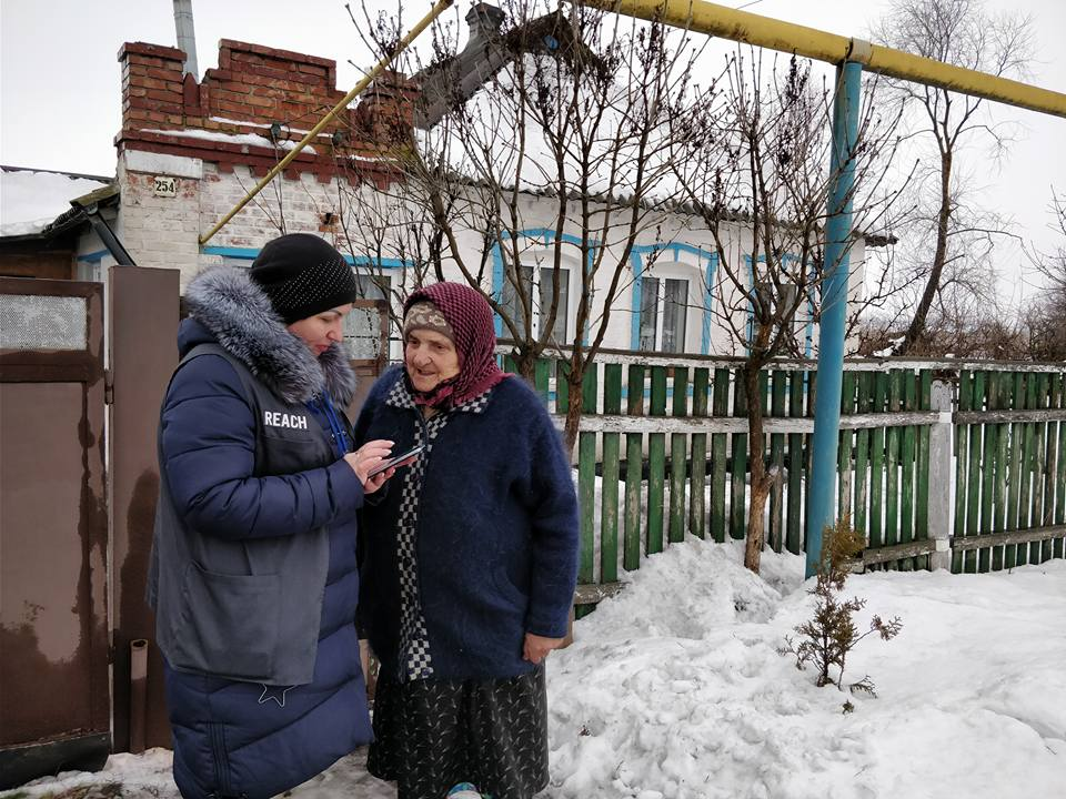 REACH team interviews a pensioner in the town of Pervomaiske near the destroyed Donetsk airport ©REACH/2018