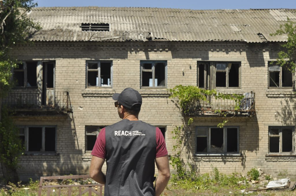 A REACH team member observes a damaged building near the contact line in Eastern Ukraine. © REACH 2018