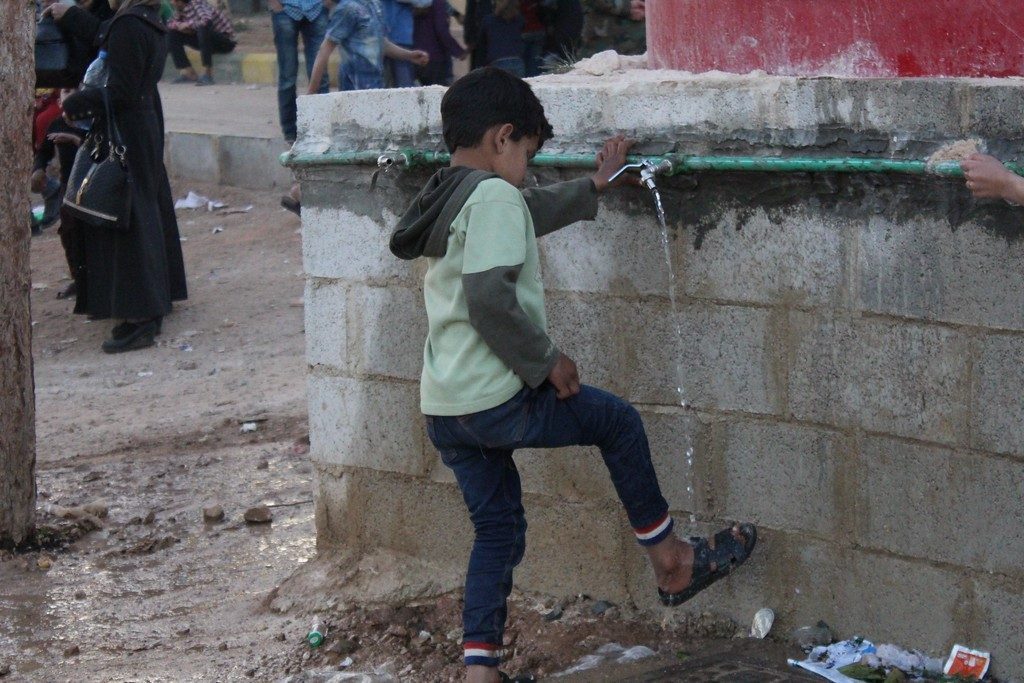 Boy washes his feet at a collective shelter for IDPs from eastern Ghouta. ©OCHA/Ghalia Seifo